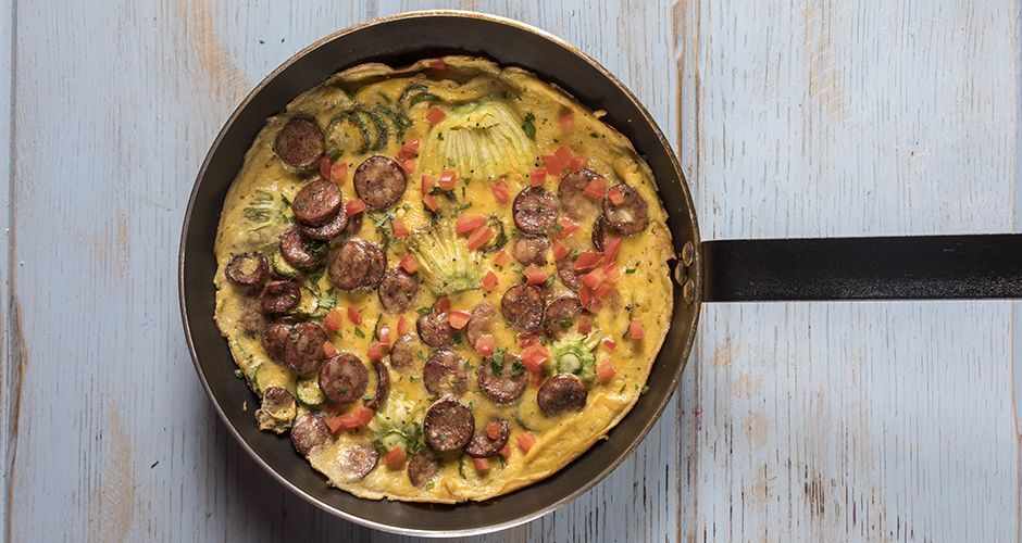Greek frutalia omelet with zucchini blossoms and sausages